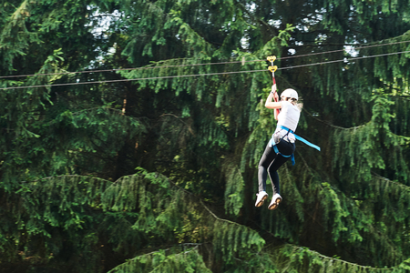 tarzan: Girl riding cableway in forest adventure and amusement high wire park. Authentic shot may be little blurred Stock Photo