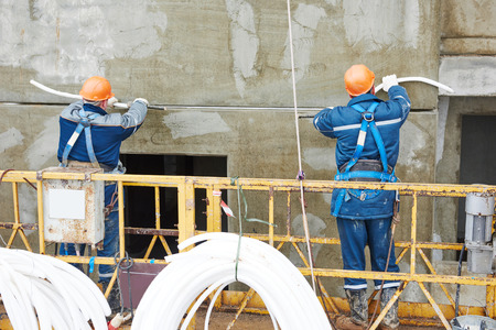 Facade plasterer workers sealing concrete slab joint seam with insulation material and putty mastic at outdoor building wall Stock Photo