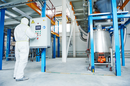 chemical industry worker operating equipment at technological industrial factory Standard-Bild
