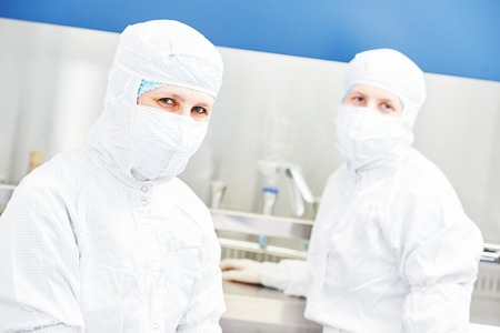 researchers: Two female science researchers in protective uniform at microbilogy laboratory Stock Photo