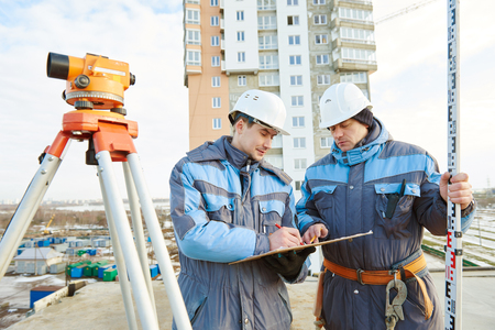 teodolito: two surveyor builders working with theodolite equipment at construction site