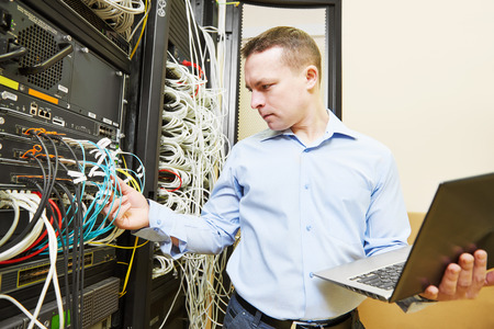 Networking administrating service. network engineer administrator checking and installing software at server hardware equipment of data center Stock Photo