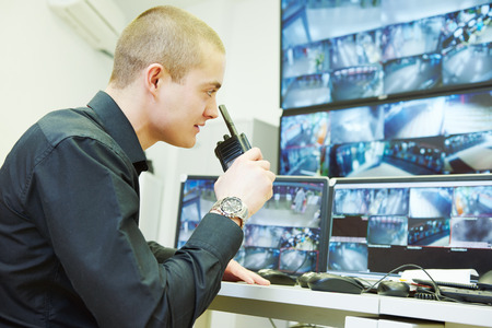 security guard officer watching video monitoring surveillance security system Imagens
