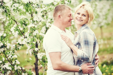 landlady: Happy adult young couple in love together in blooming apple orchard. Toned