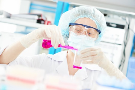 Pharmacy and chemistry theme. Female medical scientific researcher or pharmacy doctor holding flasks with pink liquid solution. Focus on face