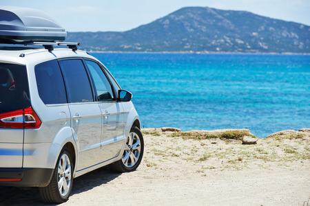 Automóvil viajar. vista en perspectiva del lado trasero del coche monovolumen, cerca de la playa del mar