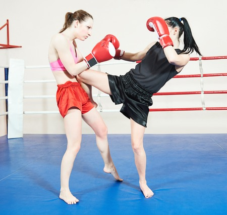 phisical: Thai kickboxing fight. Two muay thai female fighters at training boxing ring Stock Photo