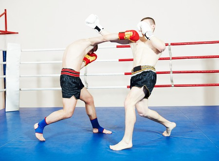 phisical: Muay thai kickboxing. Two male  boxers fighting at training boxing ring Stock Photo