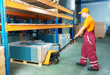 male worker in warehouse working with hand forklift photo