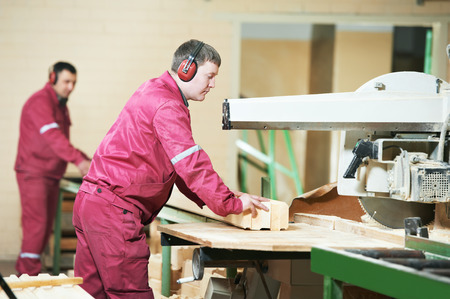 carpenter worker with circular saw machine at wood beam cross cutting during furniture manufacture Stock Photo