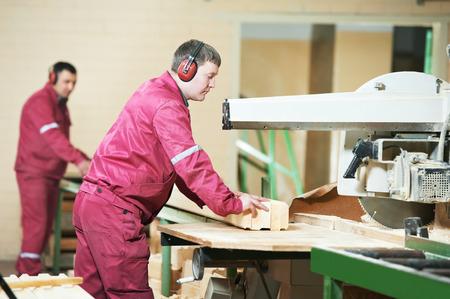 timmerman werknemer met cirkelzaag machine op een houten balk horizontale tijdens de vervaardiging van meubels Stockfoto