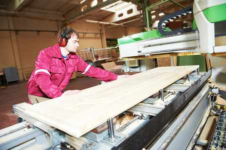 milling center: industrial carpenter worker operating wood cutting machine during wooden door furniture manufacturing Stock Photo