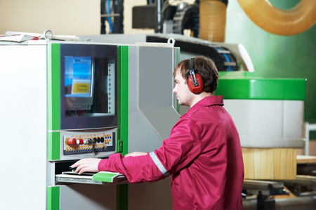 cabinet maker: industrial factory worker operating wood cutting machine during wooden door furniture manufacturing