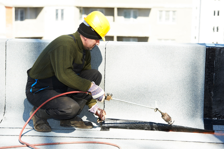roofing system: Roofer preparing part working with bitumen roofing felt roll for melting by gas heater torch flame Stock Photo