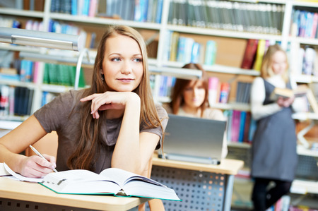 girl studying: Studying young teenage college student girl in a library with books