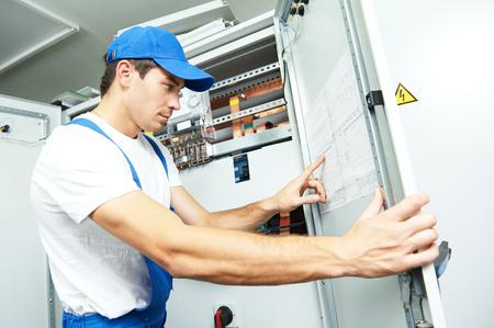 electricidad industrial: electricista trabajador de ingeniero inspector delante de equipos fuseboard en la habitación