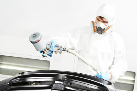 priming paint: auto painting work. Worker paints car body bumper in a paint chamber during repair work Stock Photo