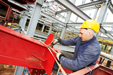 rigger: builder worker at construction site installing metal construction frames