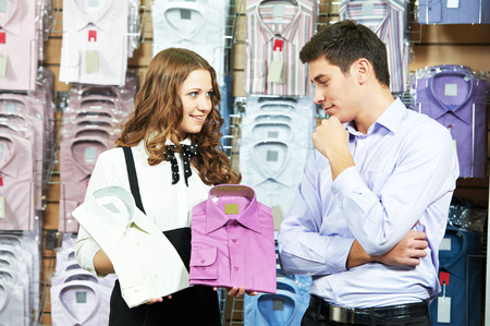 Young man choosing shirt and necktie during apparel shopping at clothing store photo