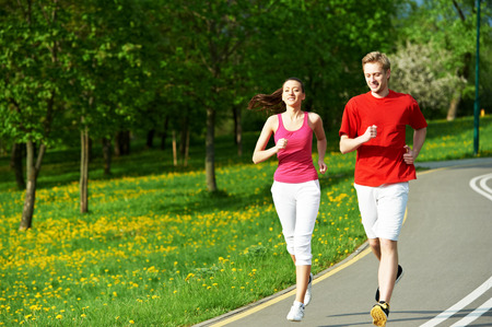 limber: Young fitness man and woman doing jogging run sport outdoors