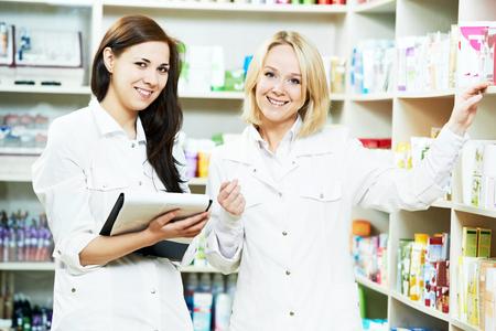recetas medicas: dos Mujeres del químico farmacéutico en discusiones sobre la medicina y la farmacia con receta en la farmacia Foto de archivo