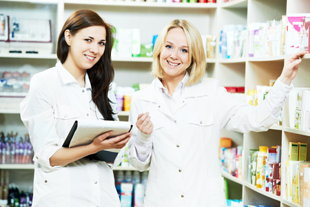 two pharmacist chemist women discussing medicine and prescription in pharmacy drugstore