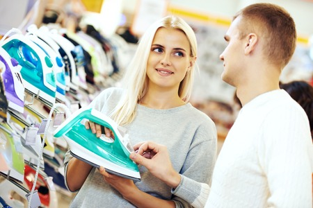 electric iron: Family Shopping. Young woman choosing electric iron in home appliance store supermarket