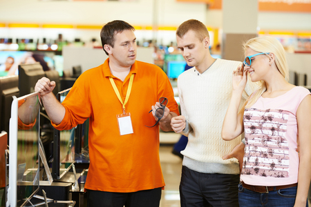 tv set: Seller assistant demonstrating 3D tv set to young family in home appliance shopping mall supermarket Stock Photo