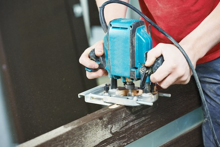 installer: door installer working with milling cutter at preparing hole for hinge Stock Photo