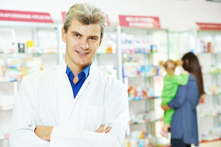 cheerful pharmacist chemist man in pharmacy drugstore