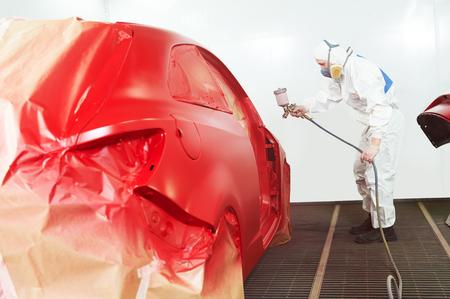 automonteur werknemer schilderij van een rode auto in een verf kamer tijdens reparatiewerkzaamheden Stockfoto