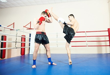 phisical: Muay Thai kickboxing. Male thai boxers fighting at training boxing ring Stock Photo