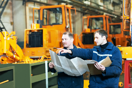 mechanician: industrial engineer workers discussing project blueprint in front of heavy industry machinery production line at manufacturing factory