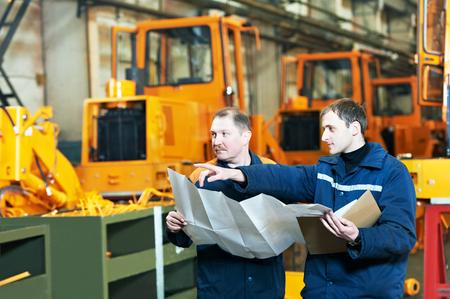 maquinaria pesada: trabajadores de ingenieros industriales en discusiones sobre plano proyecto en frente de la industria pesada maquinaria de la línea de producción en la fábrica de fabricación