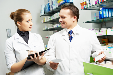Two cheerful pharmacist chemist worker working in pharmacy drugstore photo