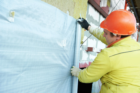 plasterer: facade plasterer builder at outdoor building external wall insulation with protection film