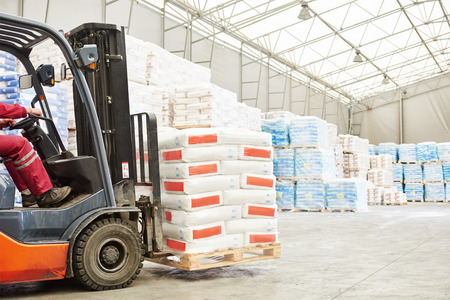 rack arrangement: warehousing. Forklift driver stacking pallets with cement packs by stacker loader