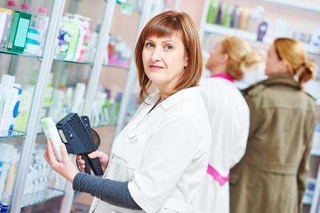 pharmacien femme utilisant un marquage pistolet étiqueteuse pour coller l'étiquette de la médecine des prix en pharmacie Banque d'images
