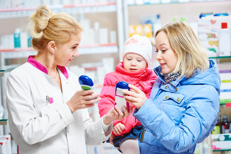 health professional: pharmacist chemist woman demonstrating vitamin to child girl with mother in pharmacy drugstore. family health Stock Photo