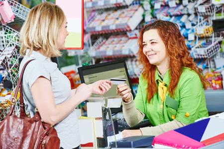 check out: Customer buyer paying with credit card at supermarket and making check out with cashdesk worker in store Stock Photo