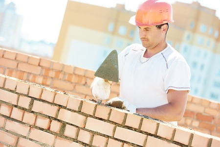 construction worker. Portrait of mason bricklayer installing red brick with trowel putty knife outdoors Stock Photo