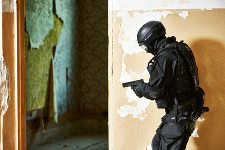 antiterrorist: Military industry. Special forces or anti-terrorist police soldier armed with pistol ready to attack during clean-up operation, mission Stock Photo