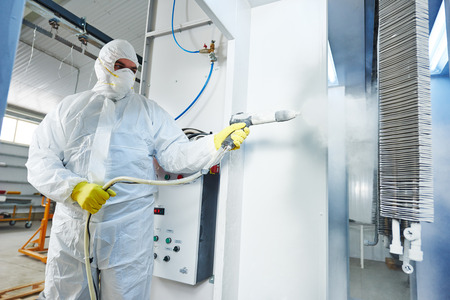industrial metal coating. Worker man in protective suit with gas mask spraying powder to steel finished parts in painting chamber Stock Photo - 61223601
