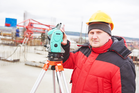 tachymeter: Surveyor working with theodolite transit equipment at construction site