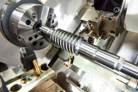 metalworking industry. cutting tool processing steel metal spiral pinion or worm screw shaft on lathe machine in workshop. Focus on tool. Imagens