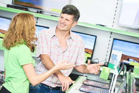 vendedor: Concepto de compras. Feliz vendedor asistente mujer ayuda comprador ordenador portátil elección en la electrónica tienda de supermercado