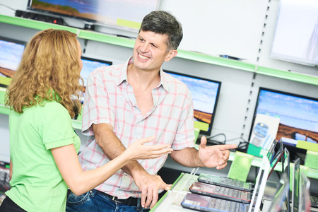 seller: Shopping concept. Happy seller assistant woman help purchaser choosing notebook computer in electronics supermarket shop