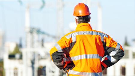 supervisi�n: supervisi�n de ingenier�a. ingeniero de servicio masculino en ropa de alta visibilidad que refleja y sombrero de pie dura al aire libre en frente de la estaci�n de calor del electropower