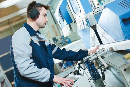 Kunststof ramen en deuren productie. Productie werknemer snijden PVC-profiel voor de ramen met dubbel glas met een cirkelzaag op industriële machine