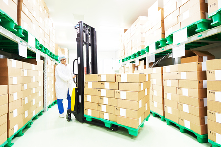 rack arrangement: warehouse worker with stacker loader truck at work. man blurred in motion intentionally.